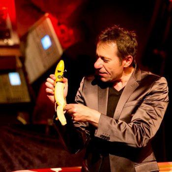 Bauchredner mit einer Puppe als Banane