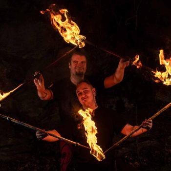Feuer-Kuenstler mit 2 brennenden Stäben in der Hand