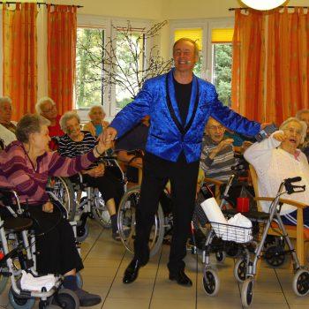 der Künstler steht in der Mitte zwischen vielen Senioren