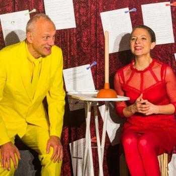 Kabarettist mit einem gelben Anzug auf der Bühne