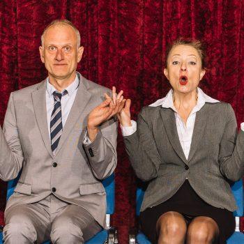 Zwei Kabarettisten sitzend auf einem Stuhl