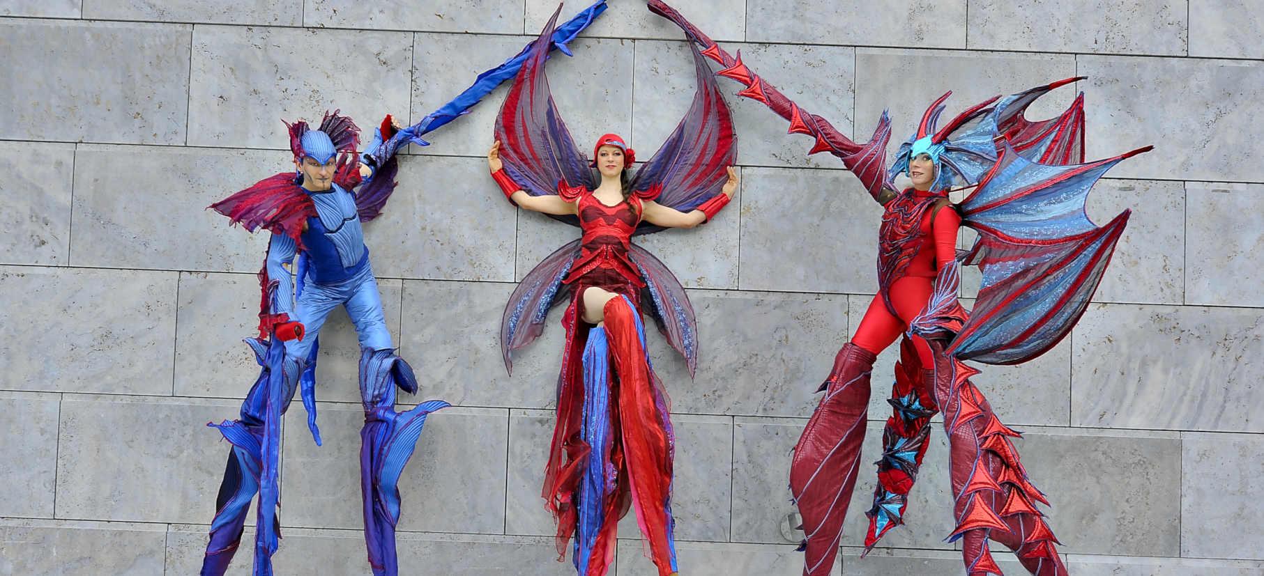Drei Stelzenkünstler als Drachen verkleidet