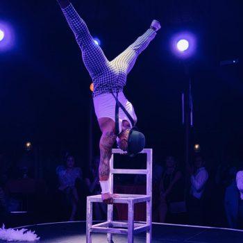 Stuhlakrobatik der Akrobat im Handstand auf Stühlen