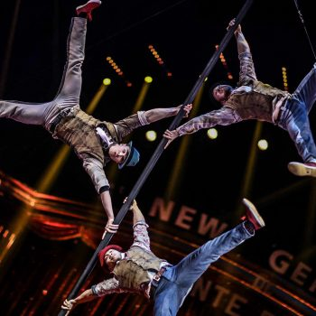 3 Akrobaten hängen an einer Stange