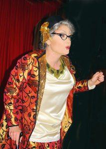 Travestiekünstler als alte Frau mit Tasche