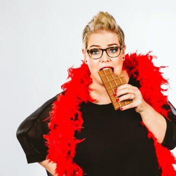 Die Komikerin hält eine Tafel Schokolade in der Hand