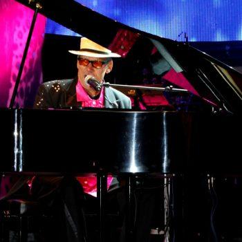 Das Elton John Double sitzt an einem Klavier und singt in ein Mikrofon.