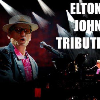 Das Elton John Double sitzt vor einem Klavier und trägt einen Hut, eine Sonnenbrille und einen pink schwarzen Anzug.