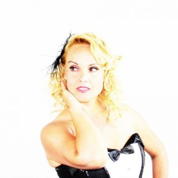 Das Marilyn Monroe Double in einem schwarz weißen Kleid und mit Federschmuck in den Haaren.