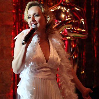 Das Double hält ein Mikrofon und trägt ein weißes Kleid, sowie eine weiße Federboa.