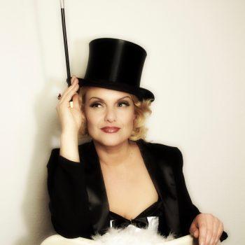 Marlene Dietrich Double auf der Couch mit Zylinder und Zigarettenspitze