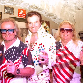 Ein Mann in Elvis Kostüm steht zwischen zwei weiteren Männern der Boogie Band.