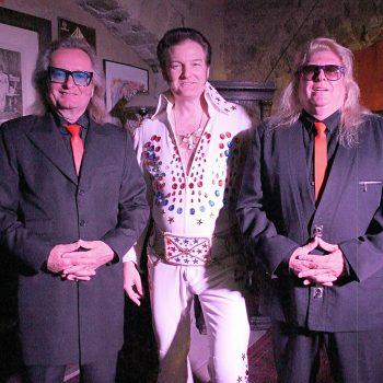 Links und rechts stehen 2 Männer der Boogie Band in schwarzen Anzügen mit roten Krawatten. Dazwischen steht der Elvis Imitator.