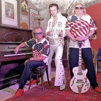 Links siezt ein Mann an einem Klavier, daneben steht der Elvis Imitator und ganz rechts ein anderer Mann der Boogie Band mit einer Gitarre in der Hand.