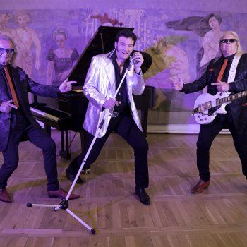 Ein Mitglied der Boogie Band steht vor einem Klavier, daneben steht das Elvis Double an einem Mikrofon und rechts ist noch ein Mann mit einer Gitarre um den Hals.