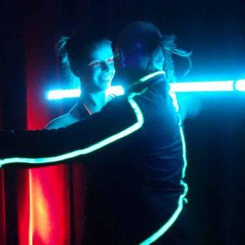Ein paar Tanzt bei der Lichtshow und Schwarzlichtshow