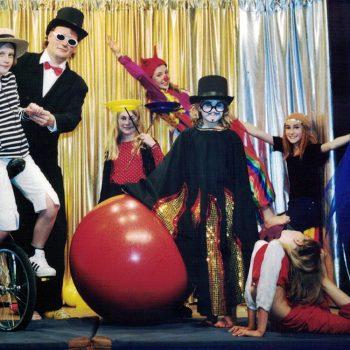 Der Zirkus Direktor mit mehreren Kindern auf der Bühne.
