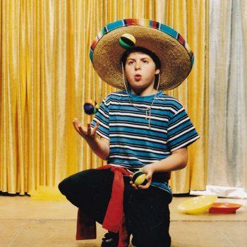 Ein Kind der Zirkus Mitmachshow jongliert mit 3 Bällen und hat einen mexikanischen Hut auf dem Kopf.