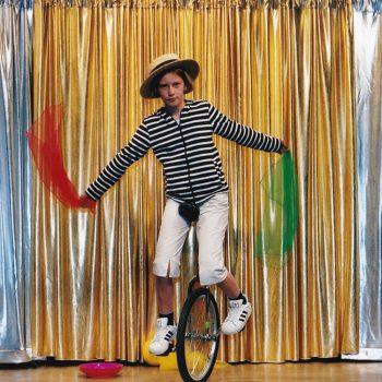 Ein Kind der Zirkus Mitmachshow fährt auf einem Einrad und hat bunte Tücher in der Hand.