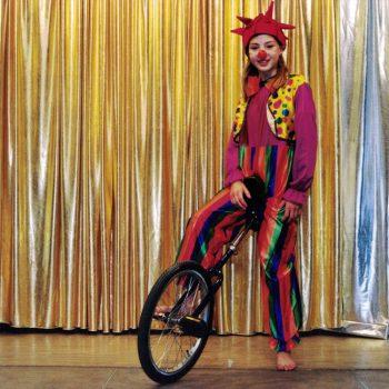 Ein Kind sitzt auf einem Einrad und trägt ein buntes Clown Kostüm.