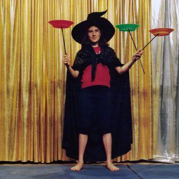 Ein Kind, in einem Hexen Kostüm, balanciert Teller, die auf Stäben stehen.